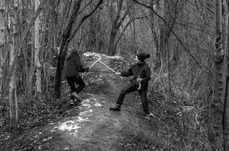 kids_playing_with_sticks_in_the_forest